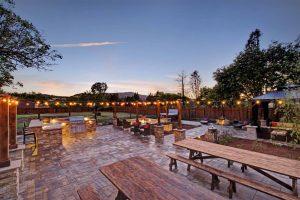 Picnic tables and stone patio at dusk at Casa Bella Kenwood