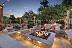 Casa Bella firepit with flames and outdoor kitchen/living area